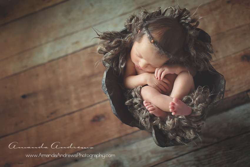 sleeping newborn in wood bowl