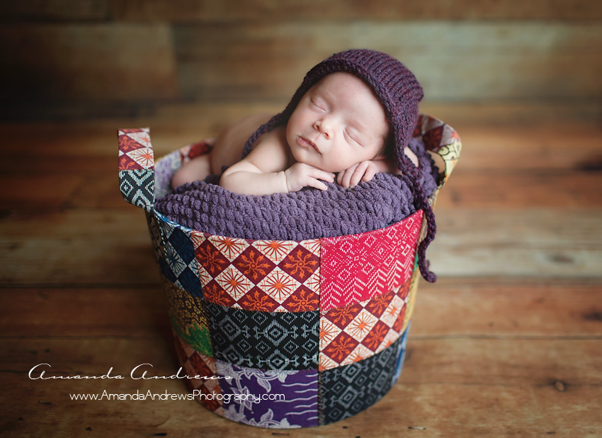 baby girl sleeping in colorful basket