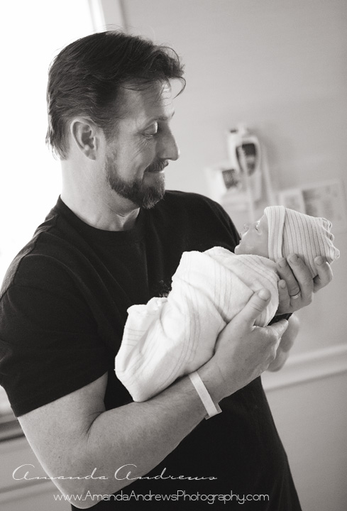 photo of dad holding brand new baby